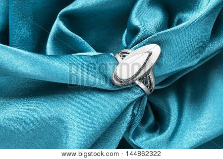 Vintage nacre ring on crumpled blue satin as a background