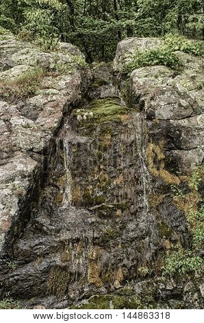 Beautiful springtime waterfall trickle on ancient rock wall