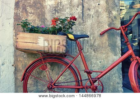 Flowers in a wooden box in the trunk of a red dyeing bike parked in the concrete walls of the house