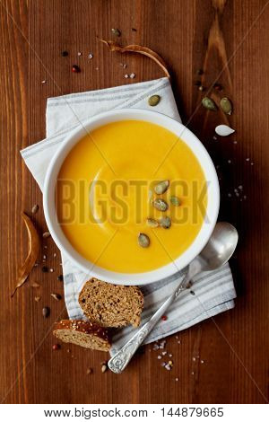 Pumpkin soup with rye bread in white bowl. Dietary vegetable and healthy food. Top view, flat lay.