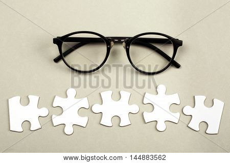 Disconnected white jigsaw puzzle pices with eye glasses. Business and teamwork concept.