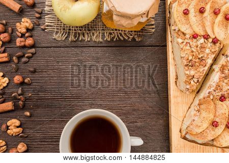 Cup of tea and homemade pie covered with apples, cinnamon, foxberry and nuts on the dark wood table