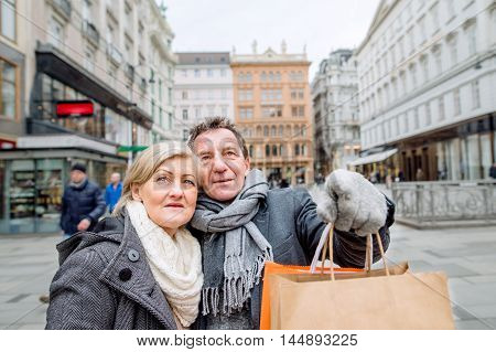 Senior Couple Shopping In Centre Of The City. Winter