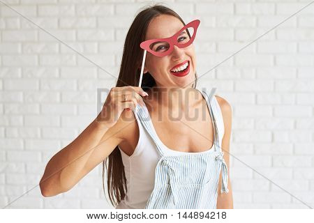 Happy smiling woman wear white singlet with overalls and holding red glasses-mask, white brick wall on background