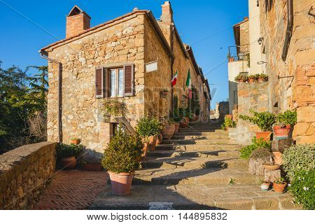 Small Old Mediterranean town - narrow street in Pienza with sunlight and flowers, Tuscany,  Italy, Europe