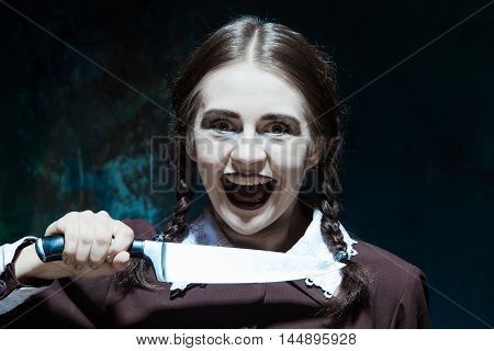 Portrait of a young girl with knife in school uniform as killer woman against school board . The image in the style of Halloween