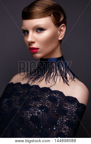 Beautiful girl in the style Gatsby with a collar of feathers and lace blue dress. Model with the hairstyle from the 20s of the 20th century. Beauty face. The photo was taken in a studio.
