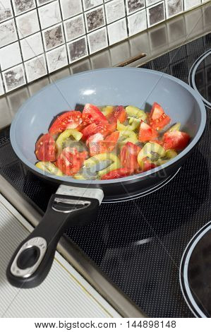 Chopped vegetables in a frying pan on the electrical stove
