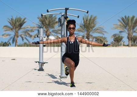 Woman of african ethnicity uses outdoor gym equipment for outside sport activity. Exercise with suspension trainer