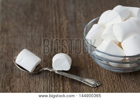 White soft marshmallows in glass bowl on rustic wooden background, selective focus.