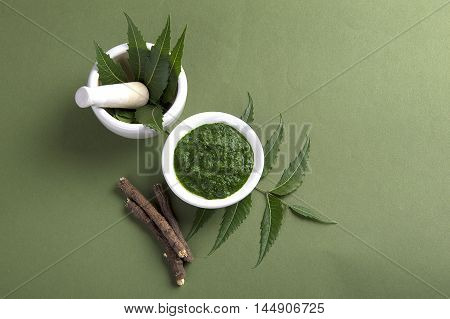 Medicinal Neem leaves in mortar and pestle with paste and twigs on green background