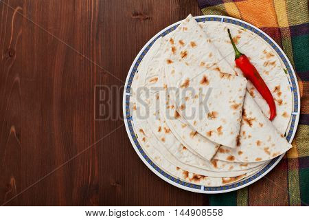 Mexican flatbread tortilla in plate on wooden table, top view. Copy space for text.