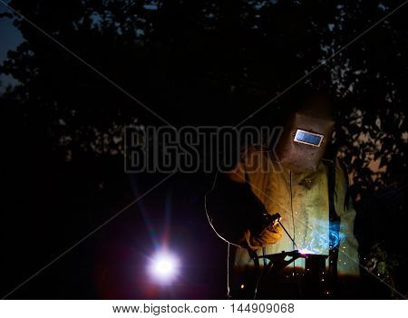 welder worker welding metal by electrode with bright electric arc and sparks during manufacture of metal equipment