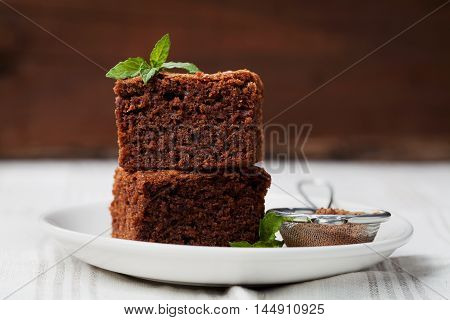 Brownie stack closeup, chocolate cake in plate on rustic wooden table.