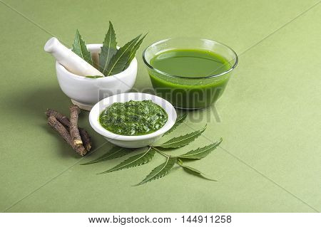 Medicinal Neem leaves in mortar and pestle with neem paste, juice and twigs on green background