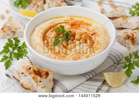 Hummus or houmous appetizer, made of mashed chickpeas with tahini, lemon, garlic, olive oil, parsley and paprika.