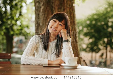 Young Woman Relaxing At Outdoor Cafe