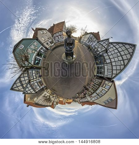 Small Planet. Statue Of A Woman In The Town Square