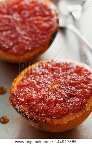 Vintage image of broiled grapefruit with brown sugar and cinnamon on metal surface. Healthy dessert is good for breakfast or snack.