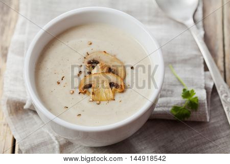 Cream soup with mushrooms champignon and potato in white bowl. Vintage style.