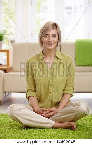 Glückliche Frau sitzt mit den Beinen überquerte am Boden des Wohnzimmers, Blick in die Kamera.?