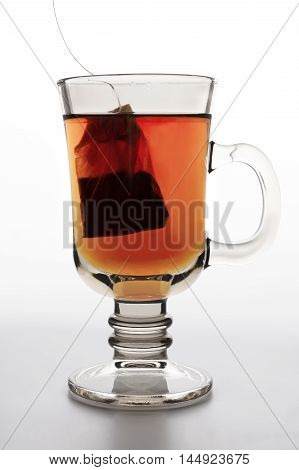 close up of brown glass tea cup with water and drawstring tea bag isolated over white