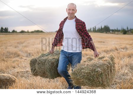 Portrait Of Farmer And Harvest. Strawbale In Hands