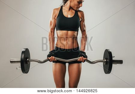 Muscles Bulging On Arms Of Woman Using Barbell