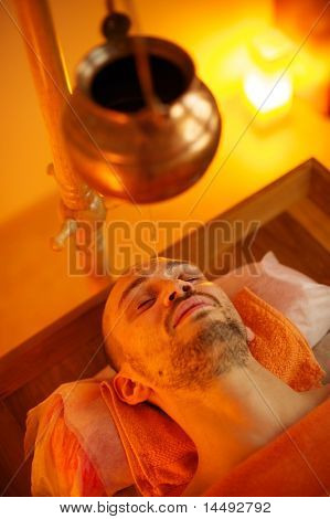Man having a shirodhara massage in a salon poster