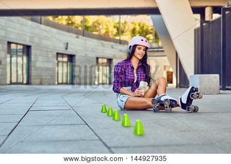 Sport girl resting after rollerblading slalom and drinking coffee. Happy teenager on rollerblading sitting on street a sunny day. Active lifestyle.
