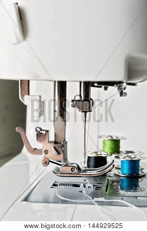 Close up view of sewing machine with reels threads, needle work concept
