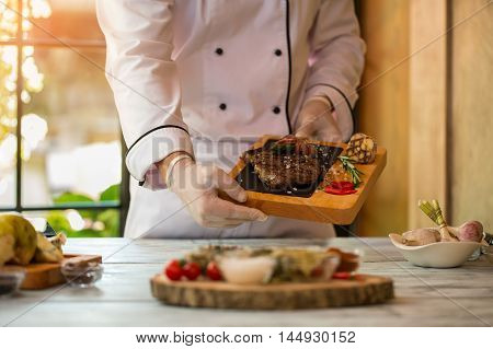 Hands hold board with meat. Rosemary and chili peppers. Appetizing ribeye steak. Skills of professional cook.