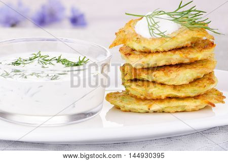 Fritters of zucchini and carrots with yogurt sauce