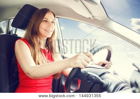 Young Lady In Red Dress Driving A Car.