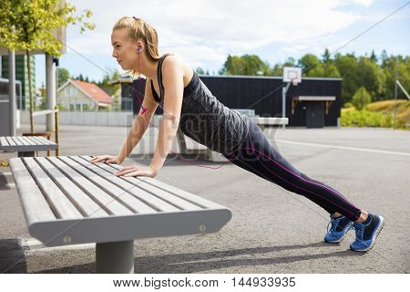 Full length side view of young woman doing pushups on bench in park