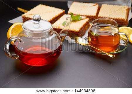 Sweet Waffle Triangular Cakes With Condensed Milk And Fresh Hot Black Tea On A Black Table