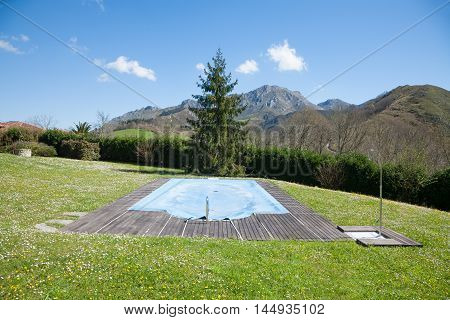 landscape of green meadow with swimming pool closed and covered with blue tarp in Spring rounded by mountains in Nature in Asturias Spain Europe