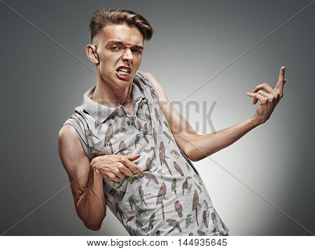 Emotional portrait of a teenager  playing on air guitar on a gray background