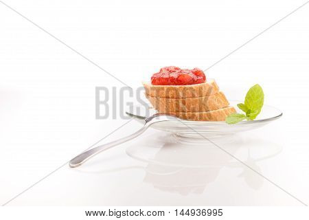 Beautiful studio food shot of baguette with plumb jam on the glass plate with a tea spoon.
