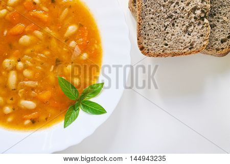Cooked beans served in white plate with basil leaves and whole wheat bread on white background. Top view with copy space
