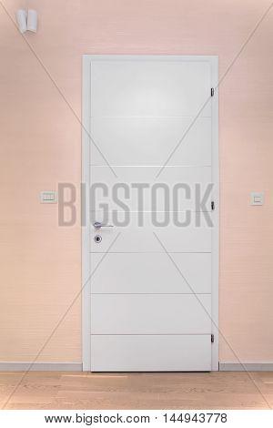 White wooden closed door inside modern interior