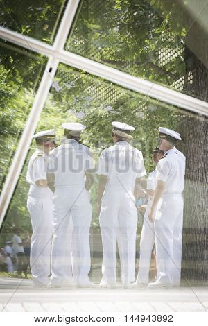 NEW YORK MAY 27 2016: Reflections of US Navy sailors in the glass of the National September 11 Museum as they gather for the military re-enlistment and promotion ceremony during Fleet Week 2016.