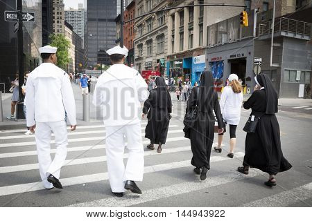 NEW YORK MAY 27 2016: US Navy personnel and Catholic nuns walk across Greenwich St after the re-enlistment and promotion ceremony at the National September 11 Memorial site during Fleet Week 2016.
