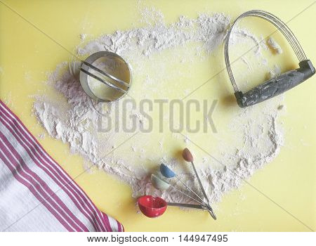 Pastry cutter, biscuit cutter, and measuring spoons on a kitchen counter with flour and a kitchen towel.