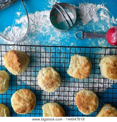 Biscuits and baking tools on a blue kitchen counter with flour. Biscuits on a black rack with pastry cutter, biscuit cutter, and measuring spoons.
