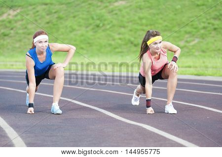 Two Caucasian Sportswomen in Professional Sportsgear Standing Prepared to Run On Sport Venue Outdoors. Horizontal Image
