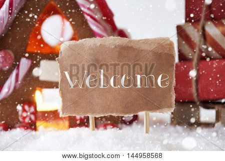 Gingerbread House In Snowy Scenery As Christmas Decoration. Sleigh With Christmas Gifts Or Presents And Snowflakes. Label With English Text Welcome