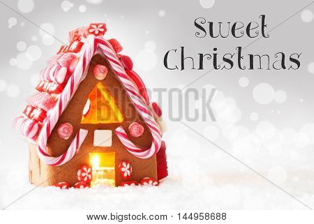 Gingerbread House In Snowy Scenery As Christmas Decoration. Candlelight For Romantic Atmosphere. Silver Background With Bokeh Effect. English Text Sweet Christmas