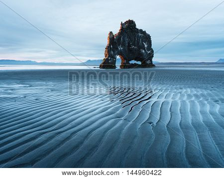 Landscape with a rock in the ocean. Beautiful lines in the sand at low tide. Tourist attraction. Hvitserkur, Iceland, Europe