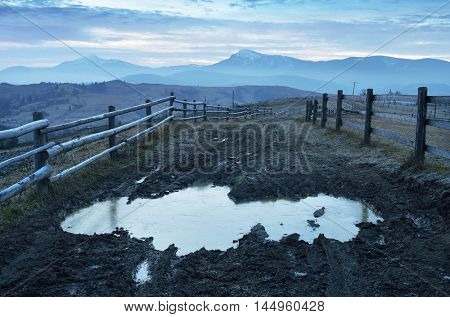 Autumn landscape frosty morning. Road with frozen puddle and swamp. Wooden fence in a mountain village. Carpathians, Ukraine, Europe